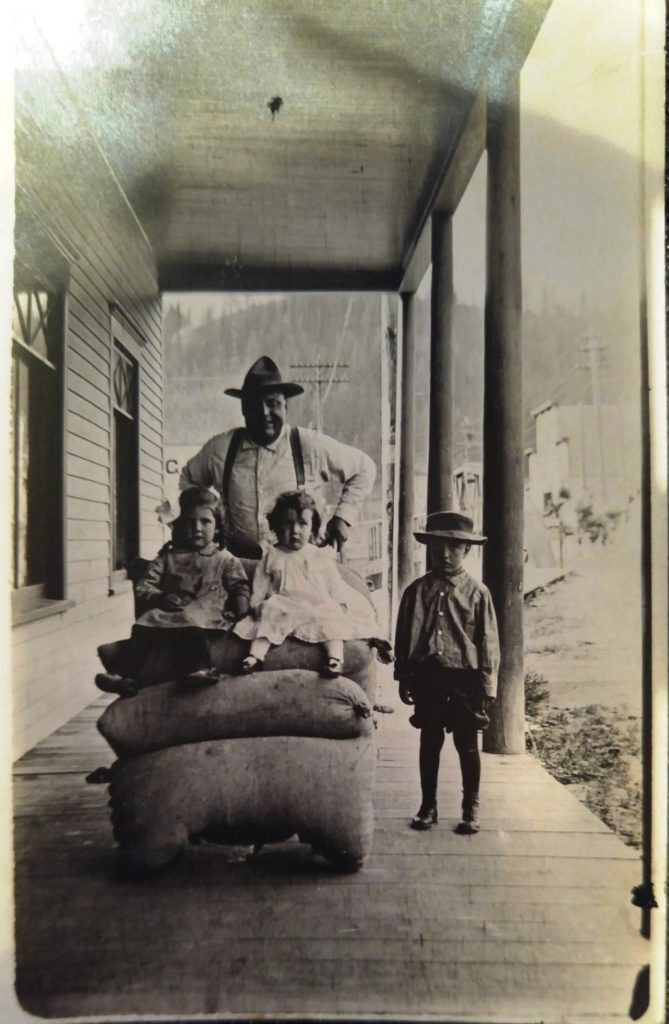John P. Harlan with children l-r: Stila Myrtle, Eda Belle and George Washington (ca. 1913) on the boardwalk at Pierce City, Idaho